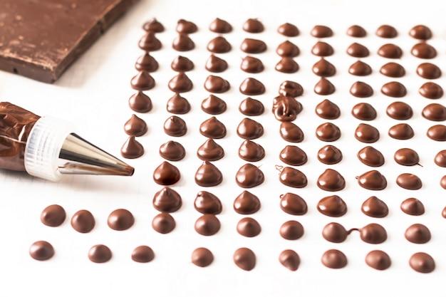 Conceito de comida fazendo lascas de chocolate caseiras para padaria em fundo branco