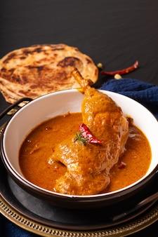Conceito de comida frango caseiro tikka masala ou curry vermelho em fundo preto