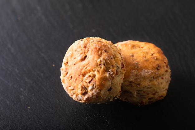 Conceito de comida fresco cozido amanteigado caseiro, salgado scones de presunto e queijo no preto