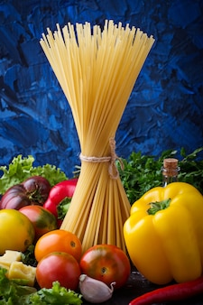 Conceito de comida italiana. massas, tomate, azeite, pimenta, salsa e queijo. foco seletivo.