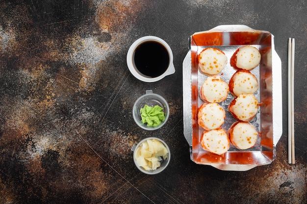 Conceito de comida japonesa. catering, vários tipos de rolos de sushi da filadélfia e rolos de camarão assados em ambiente rústico escuro
