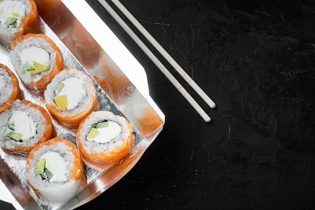 Conceito de comida japonesa. catering, vários tipos de rolos de sushi filadélfia e rolos de camarão assados definidos, em pedra preta