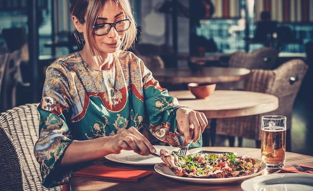 Conceito de comida jovem loira linda mulher em um vestido colorido almoça no interior do moderno