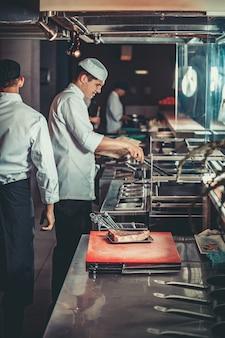 Conceito de comida, jovens chefs bonitos em uniforme branco acendem brasas e monitoram o grau de temperatura para