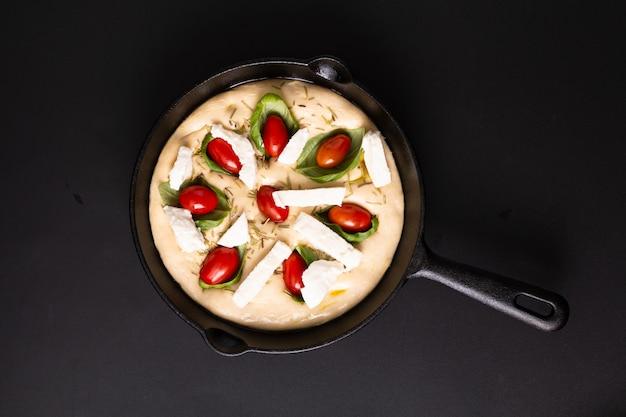 Conceito de comida levantando massa para focaccia orgânico caseiro em frigideira panela de ferro sobre fundo preto, com espaço de cópia