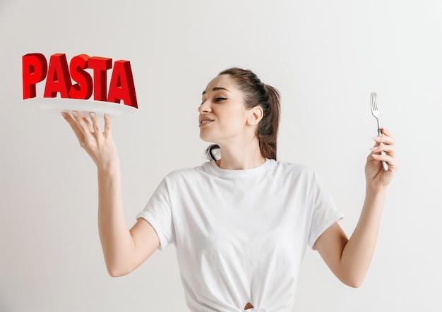 Conceito de comida. modelo segurando um prato com letras de macarrão