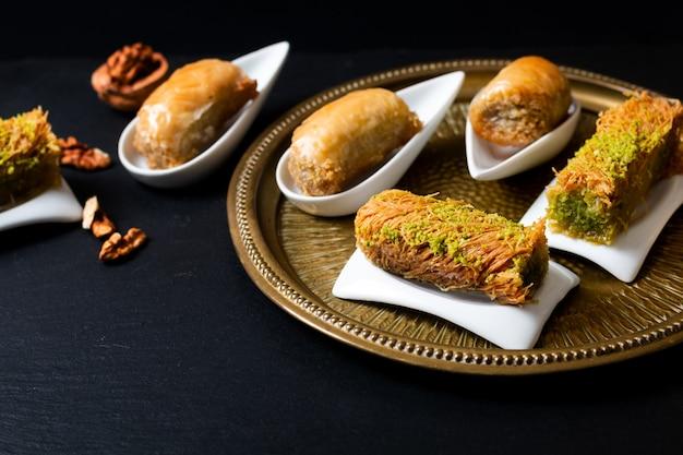 Conceito de comida nozes de baklava de sobremesa árabe oriental e rolou kanafeh na placa de ardósia preta