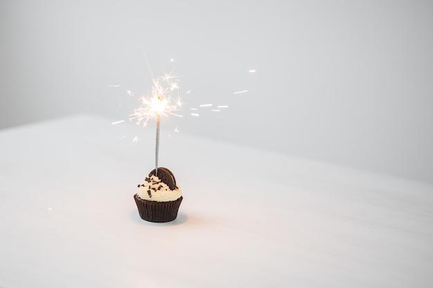 Conceito de comida, padaria, feriado, feliz aniversário e sobremesas - delicioso cupcake com espumante e