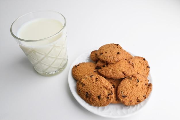 Conceito de comida, panificação e alimentação - close-up de biscoitos de aveia com chocolate e copo de leite no prato