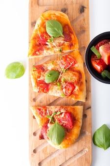 Conceito de comida pizza orgânica caseira com tomate, manjericão e presunto com espaço de cópia