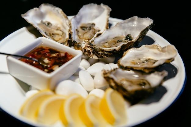 Conceito de comida. prato de ostras com molho e limão. restaurante de frutos do mar.