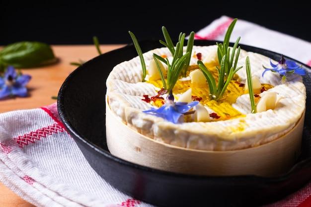 Conceito de comida queijo cremoso macio orgânico camembert francês em frigideira de ferro com espaço de cópia