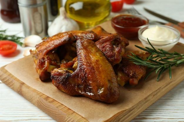Conceito de comida saborosa com asas de frango assadas em fundo branco de madeira