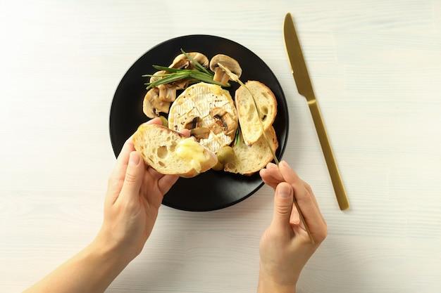 Conceito de comida saborosa com camembert grelhado no fundo branco de madeira.