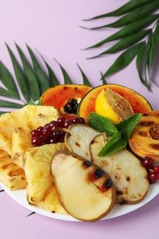 Conceito de comida saborosa com frutas grelhadas em fundo violeta.