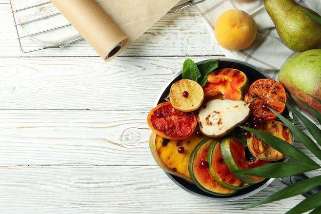 Conceito de comida saborosa com frutas grelhadas na mesa de madeira branca.