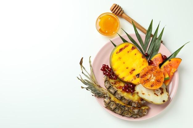 Conceito de comida saborosa com frutas grelhadas no fundo branco.