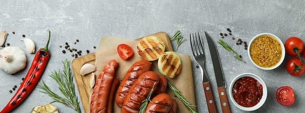 Conceito de comida saborosa com linguiça grelhada em plano de fundo texturizado cinza