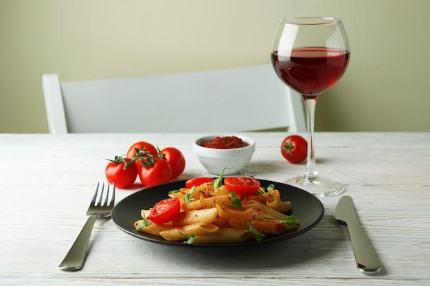 Conceito de comida saborosa com macarrão com molho de tomate na mesa de madeira branca