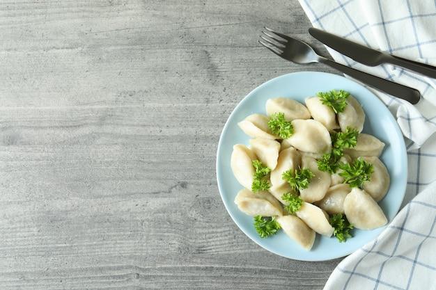 Conceito de comida saborosa com vareniki ou pierogi na mesa texturizada cinza