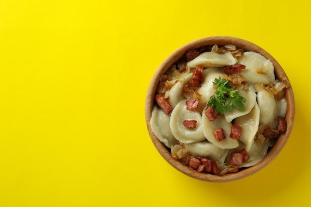 Conceito de comida saborosa com vareniki ou pierogi na superfície amarela