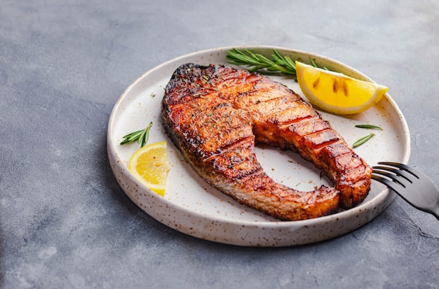 Conceito de comida saudável. bife de salmão grelhado com limão, alecrim grelhado na chapa branca sobre fundo de pedra cinza. flatlay com copyspace. conceito ômega
