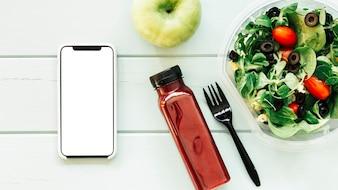 Conceito de comida saudável com smartphone ao lado de salada