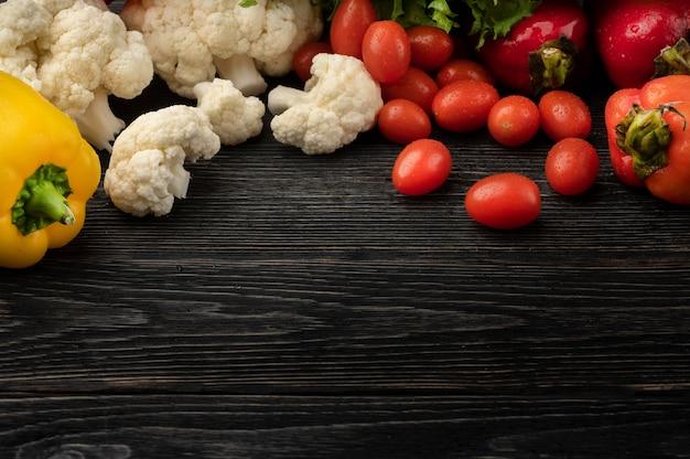 Conceito de comida saudável com vegetais em um fundo escuro de madeira com vista superior e espaço de cópia
