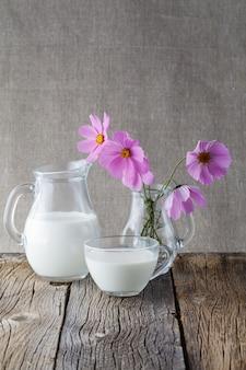 Conceito de comida saudável. copo de leite na mesa de madeira com flores