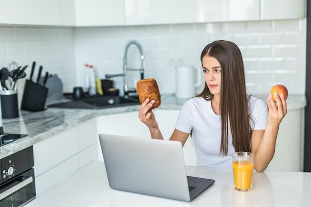 Conceito de comida saudável. escolha difícil. jovem mulher desportiva está escolhendo entre alimentos saudáveis e doces em pé na cozinha clara.