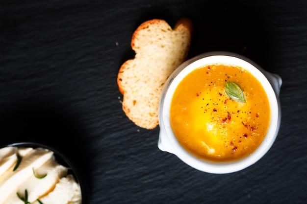 Conceito de comida saudável misture quente sopa de legumes e queijo mussarela em copo cerâmico branco