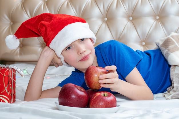 Conceito de comida saudável para o natal. alegre bonito menino branco com chapéu de papai noel encontra-se na cama ao lado de um prato de maçãs e um presente. menino pega uma maçã como símbolo de alimentação saudável