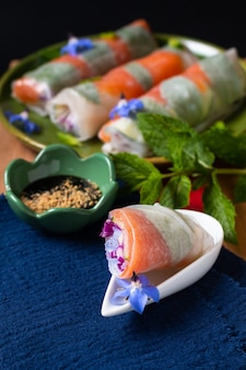 Conceito de comida saudável rolinhos primavera de papel de arroz de salmão defumado fresco com vegetais coloridos com espaço de cópia