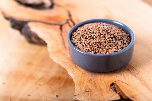 Conceito de comida saudável sementes de linho orgânico em cerâmica bolw na placa de madeira com espaço de cópia