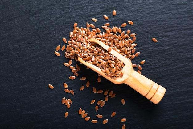 Conceito de comida saudável sementes de linho orgânico em madeira colher na placa de ardósia preta com espaço de cópia