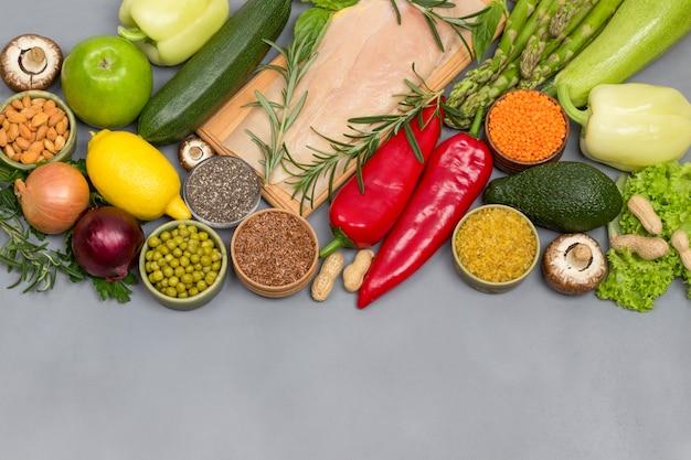 Conceito de comida saudável, sementes de vegetais verdes nozes, carne de frango em fundo cinza