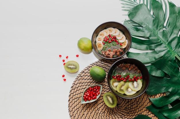 Conceito de comida saudável. vista superior na mesa com tigelas de suco. prato coberto com kiwi, granola, granada, chia, abacate.