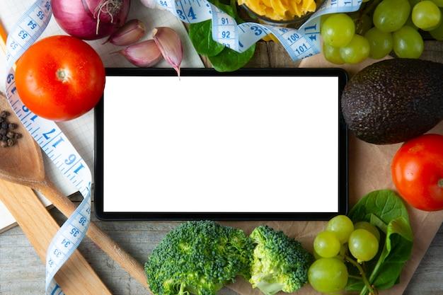 Conceito de comida saudvel. legumes frescos e tela do tablet. copie o espaço.