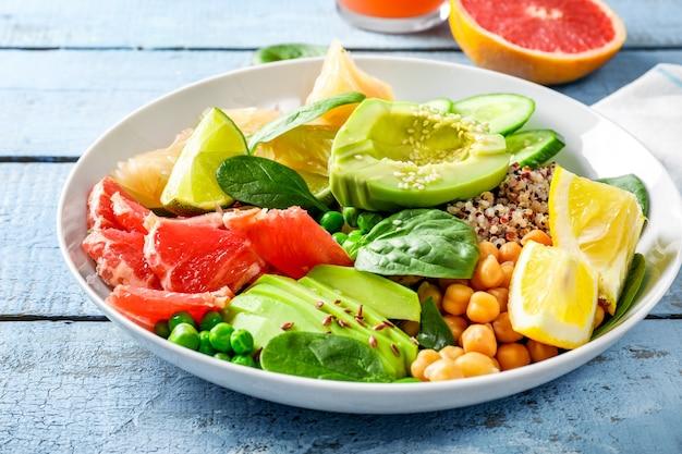 Conceito de comida vegan: quinua com abacate, pepino, ervilha, grão de bico, espinafre e frutas cítricas em fundo de madeira azul.