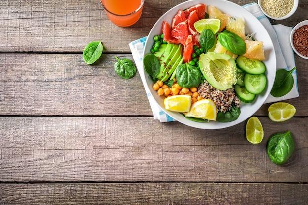 Conceito de comida vegan: quinua com abacate, pepino, ervilha, grão de bico, espinafre e frutas cítricas em fundo de madeira.
