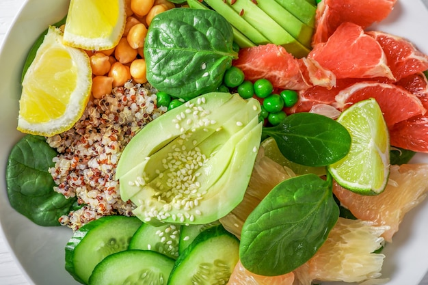 Conceito de comida vegana: quinua com abacate, pepino, ervilha, grão de bico, espinafre e frutas cítricas. vista do topo.