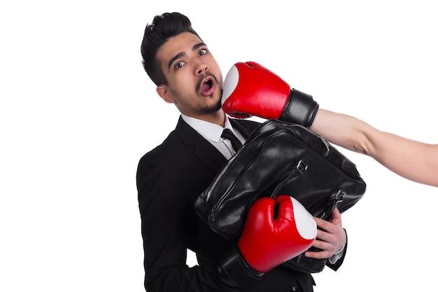 Conceito de competição de negócios, boxeador empresário, fundo branco. jovem de terno e luvas de boxe é atingido