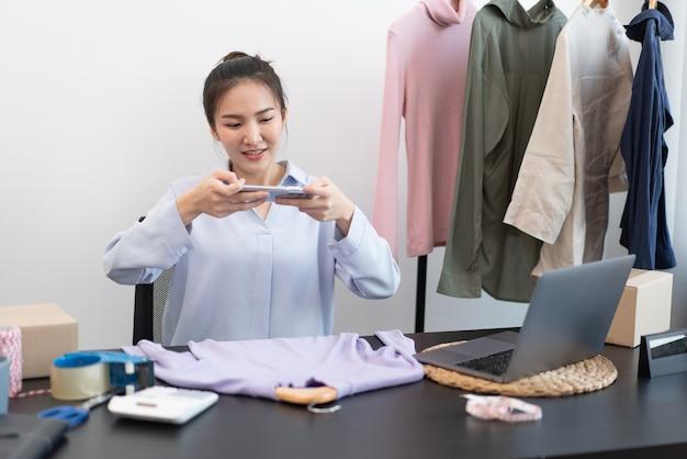 Conceito de compra ao vivo: uma vendedora online tirando uma foto de um tecido que é um produto em sua loja online.