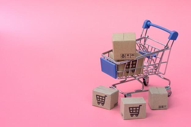 Conceito de compra: caixas ou caixas de papel no carrinho de compras azul na rosa. consumidores de compras online podem fazer compras em casa e no serviço de entrega. com espaço de cópia