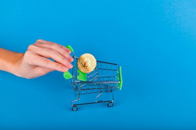 Conceito de compra de bitcoin. bitcoin no carrinho, a mão empurra o carrinho de compras onde o bitcoin está localizado.