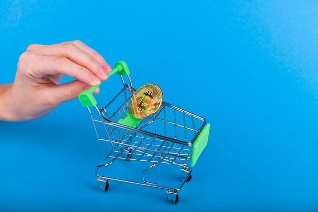 Conceito de compra de bitcoin. bitcoin no carrinho, a mão empurra o carrinho de compras
