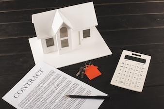 Conceito de compra de casa com contrato, chaves, calculadora e maquete sobre a mesa de madeira