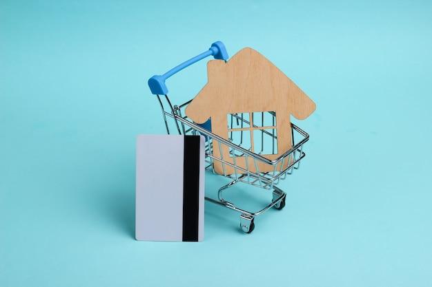Conceito de compra de casa. mini carrinho de compras, casa, cartão de crédito em fundo azul pastel