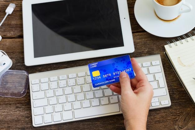 Conceito de compra móvel. entregar o escritório móvel com ipad e teclado