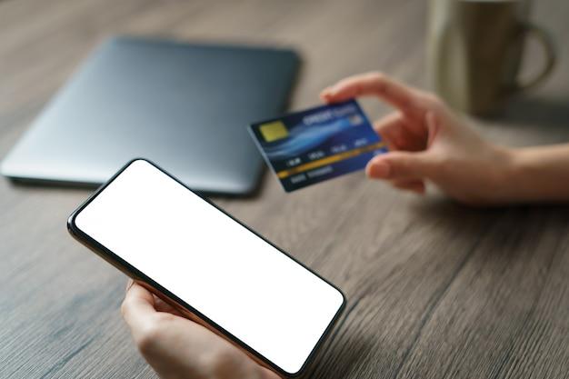 Conceito de compra on-line: mãos de mulher segurando um cartão cradit e usando compras on-line de cartão de crédito.